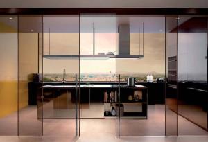 La separazione del living dalla cucina con una soluzione di grande eleganza e leggerezza che utilizza un sistema a quattro ante scorrevoli esterno muro, modello CLASSIC in vetro stratificato bronzo trasparente riflettente, prodotto da Henry Glass