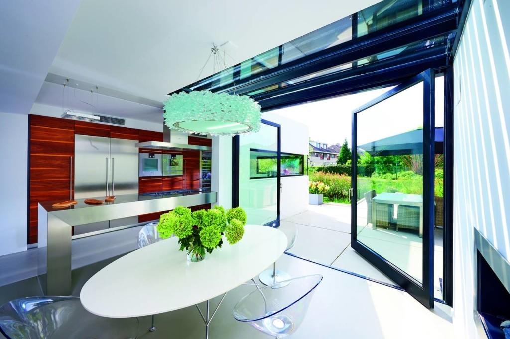 Una porta a bilico a doppia anta realizzata con profili di acciaio e vetro di sicurezza per enfatizzare la trasparenza e aprire completamente il soggiorno al giardino esterno.