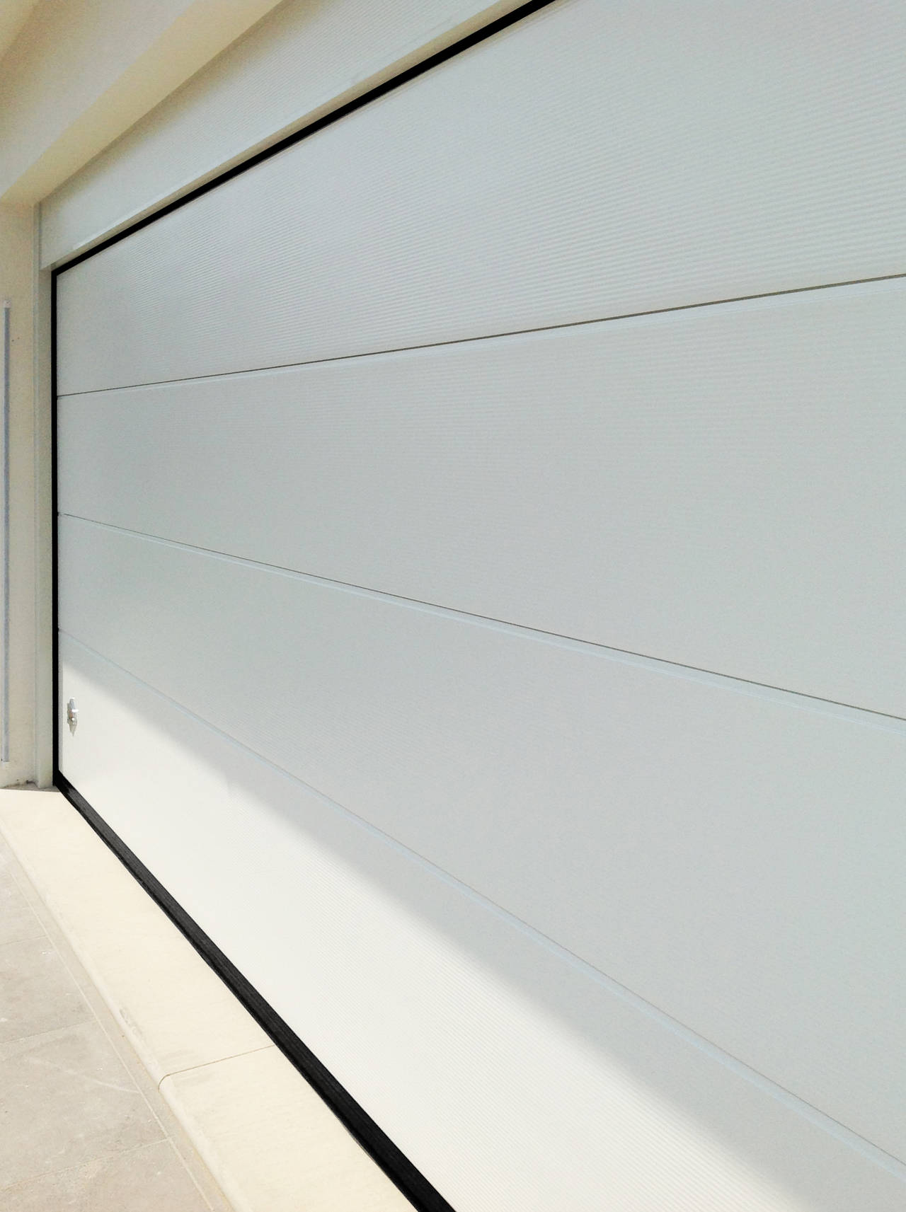Portone sezionale PERSUS di Breda con finitura Multi Rib di colore bianco con speciale motivo a onde orizzontale